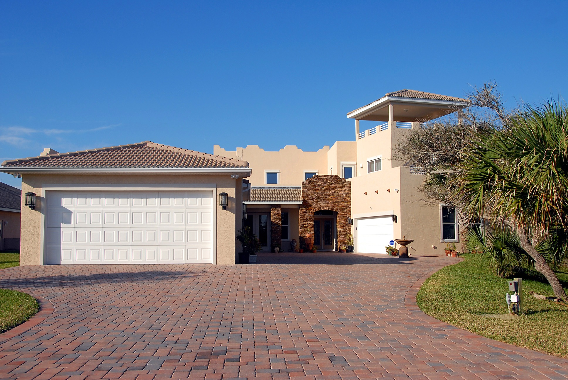 Interlocking driveway in front of beige house and blue sky